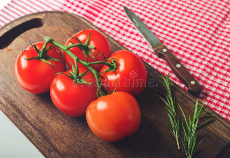 新鲜的成熟蕃茄分支在木桌上的与红色方格的毛巾,健康食品 库存照片
