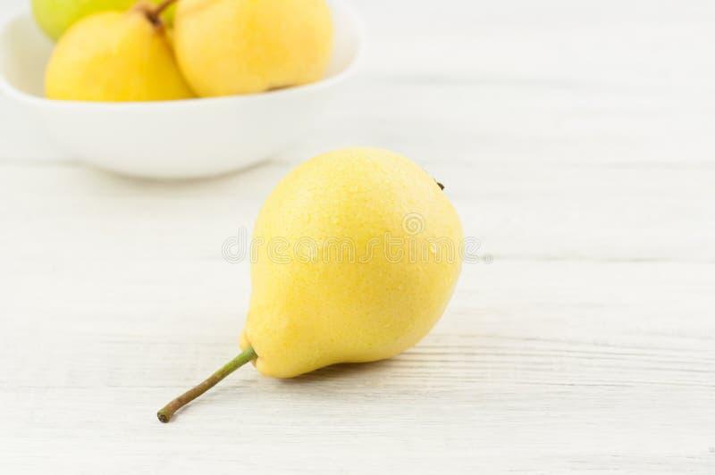 新鲜的成熟黄色整个梨堆在白色陶瓷碗和一个梨的 免版税库存照片