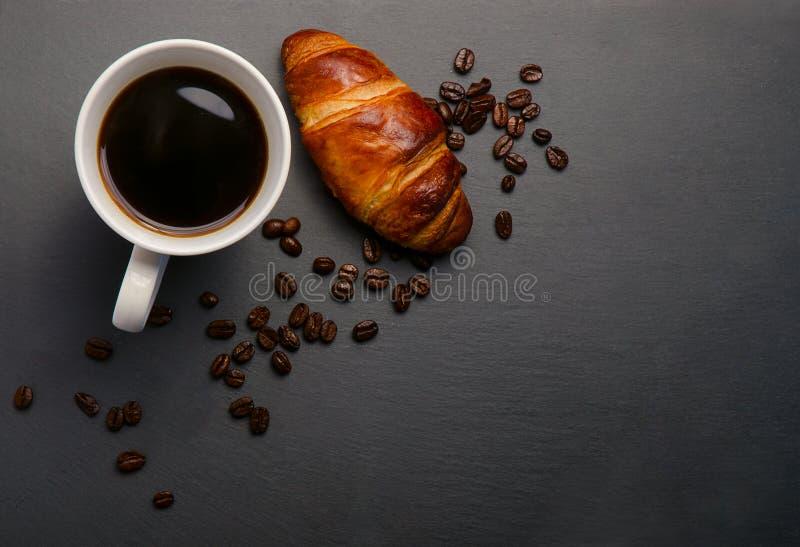 新鲜的新月形面包和咖啡在石桌上 与拷贝空间的顶视图 与一杯咖啡的可口新月形面包,烤豆 免版税库存照片