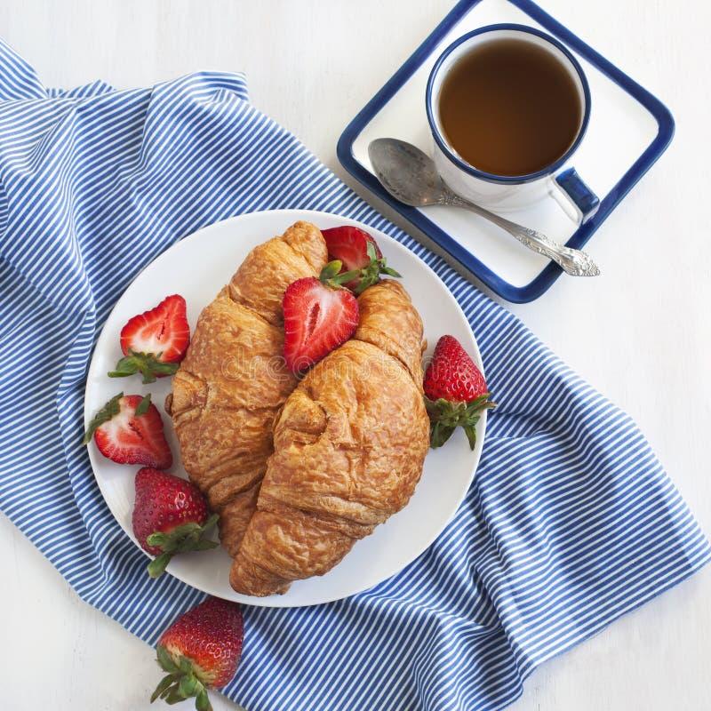 新鲜的新月形面包和茶 免版税库存照片