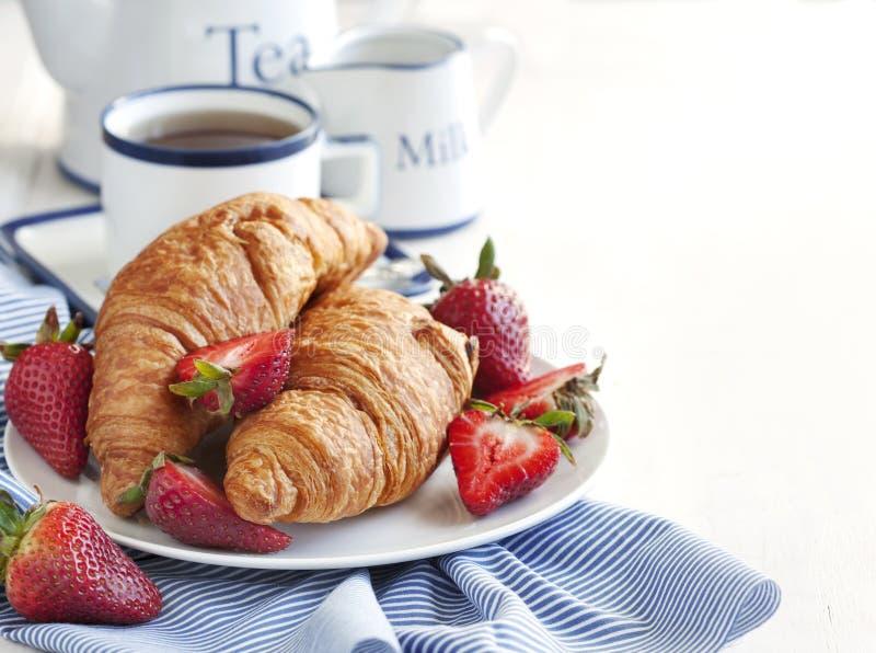 新鲜的新月形面包和茶 免版税库存图片