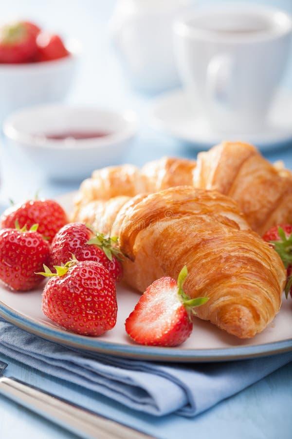 新鲜的新月形面包用果酱和草莓早餐 库存图片