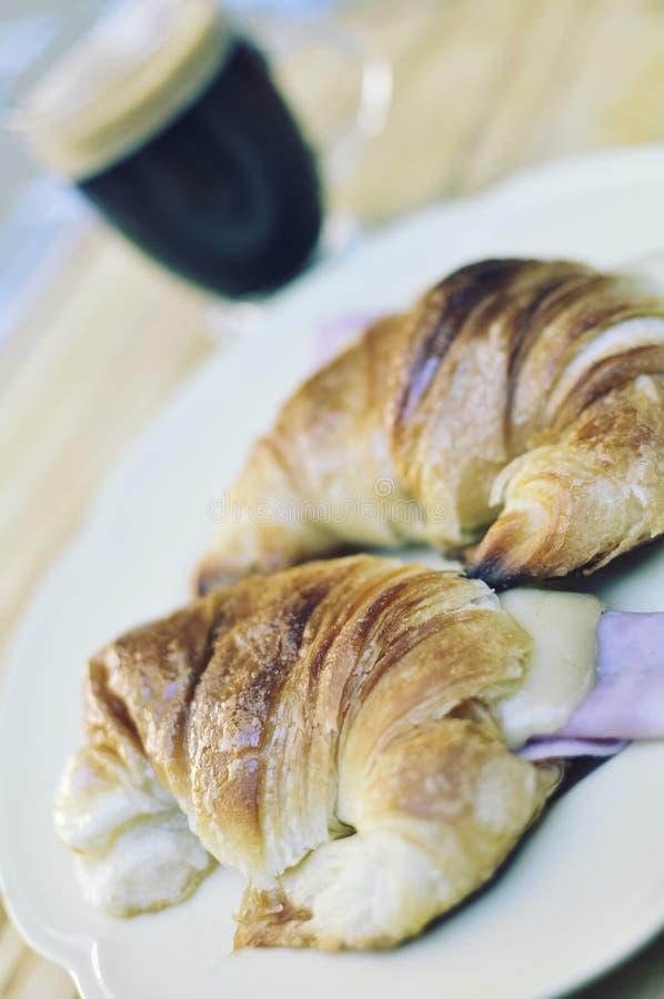 新鲜的新月形面包用火腿和乳酪在板材和咖啡 免版税库存照片