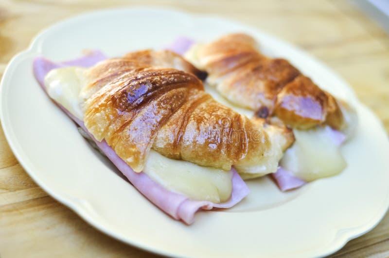 新鲜的新月形面包用火腿和乳酪在板材 免版税库存照片