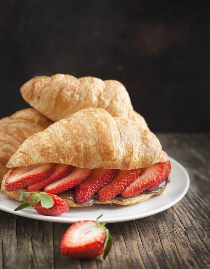 新鲜的新月形面包用草莓。 免版税库存图片