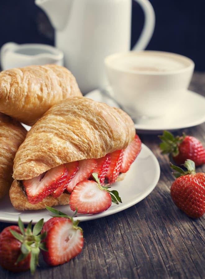 新鲜的新月形面包用草莓。 库存图片