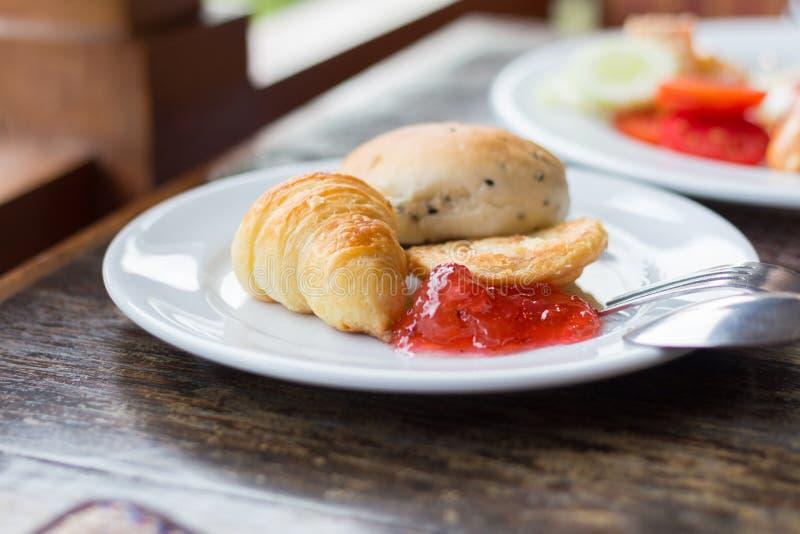 新鲜的新月形面包用草莓酱 免版税库存照片