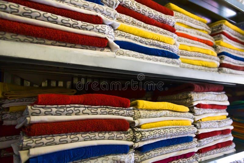 新鲜的旅馆毛巾和床单在架子被堆积 库存图片