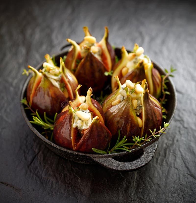 新鲜的无花果充塞用戈贡佐拉乳酪、松果和草本在一个黑盘在黑暗,石地面 免版税图库摄影