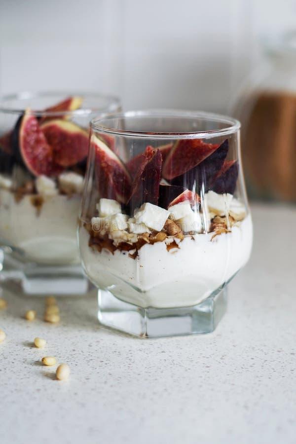 新鲜的无花果用香草鞭打了奶油、乳酪、坚果和枫蜜在一个玻璃烧杯 健康的饮料 健康食物,节食和 库存图片