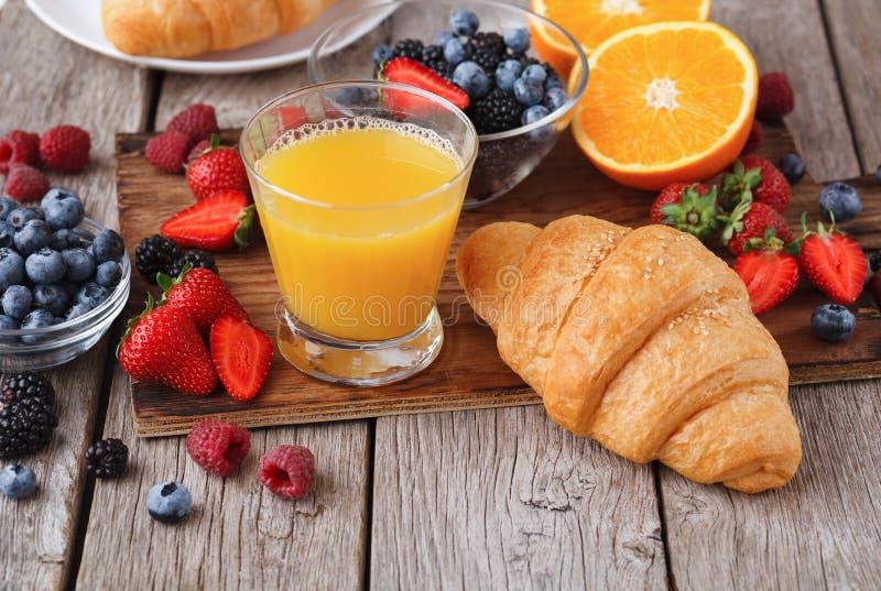新鲜的有壳的新月形面包和橙汁早晨饭食的 库存照片