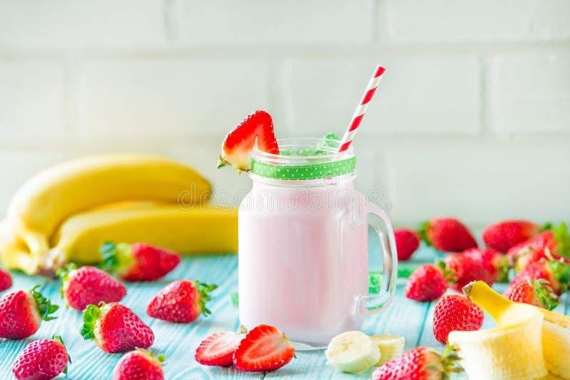 新鲜的有机农夫草莓和香蕉倾吐从在瓶子玻璃的瓶的奶昔 库存图片