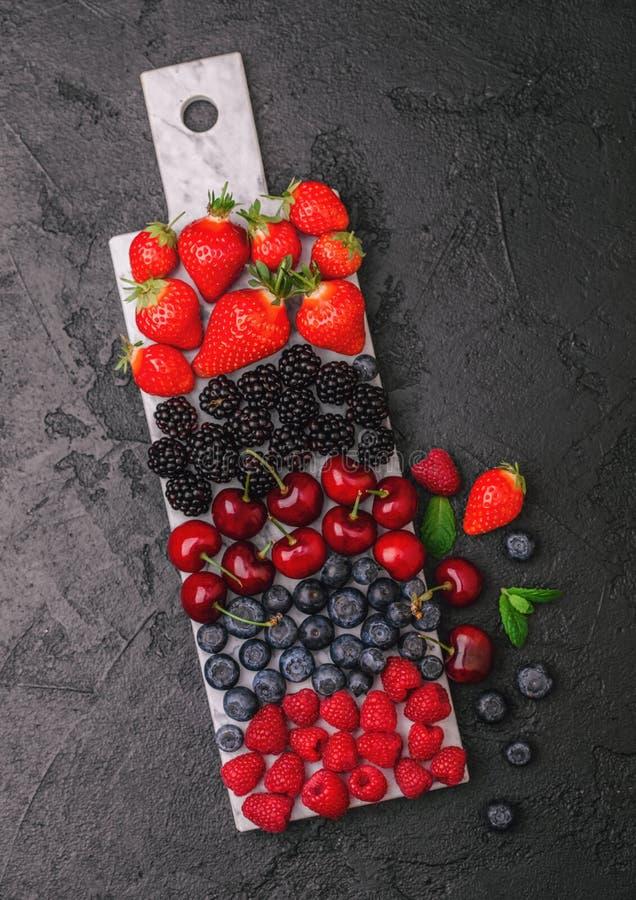 新鲜的有机夏天莓果在黑暗的厨房用桌背景的白大理石委员会混合 莓,草莓,蓝莓, 免版税库存图片