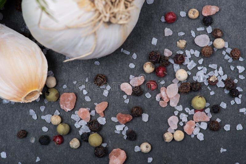 新鲜的有机大蒜、粗糙的海盐、喜马拉雅桃红色盐和彩虹干胡椒在黑暗 图库摄影