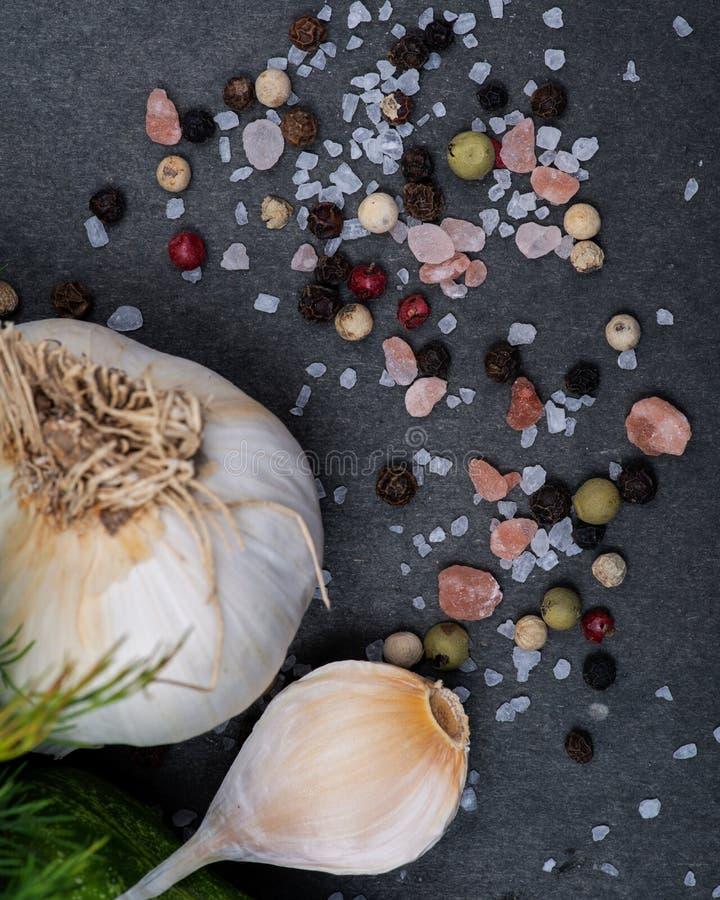 新鲜的有机大蒜、粗糙的海盐、喜马拉雅桃红色盐和彩虹干胡椒在黑暗 免版税库存图片