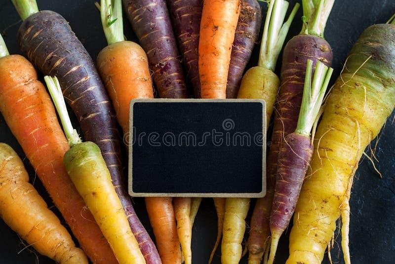 新鲜的有机彩虹红萝卜和一个小黑板 免版税库存照片