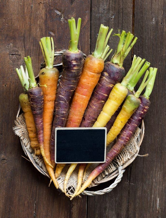 新鲜的有机彩虹红萝卜和一个小黑板 库存图片