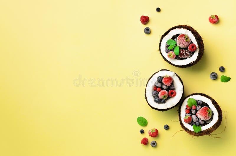 新鲜的有机莓果,在黄色背景的薄荷叶里面成熟椰子与拷贝空间 顶视图 流行艺术设计 库存图片