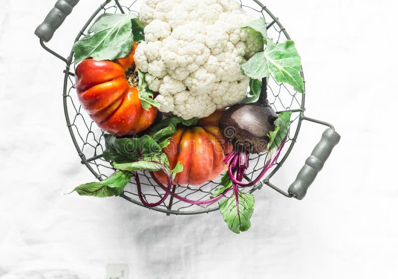 新鲜的有机菜-花椰菜,祖传遗物蕃茄,在葡萄酒的甜菜金属化在轻的背景的篮子 免版税库存照片
