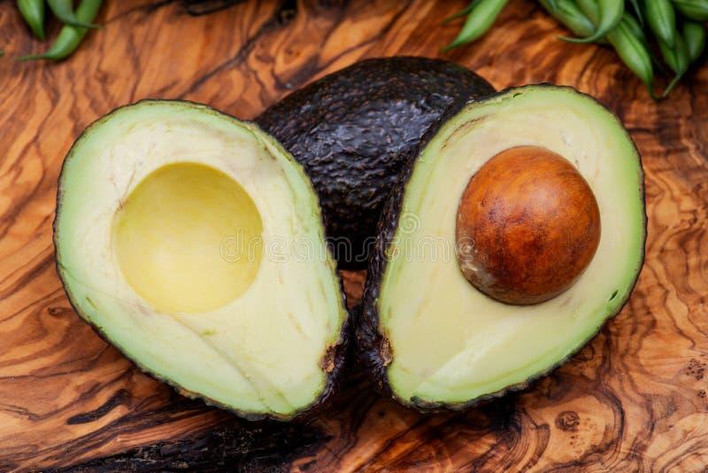新鲜的有机鲕梨在橄榄色的木头切成了两半安排 在樟科家庭的鳄梨属美国 鳄梨 Alligato 库存照片