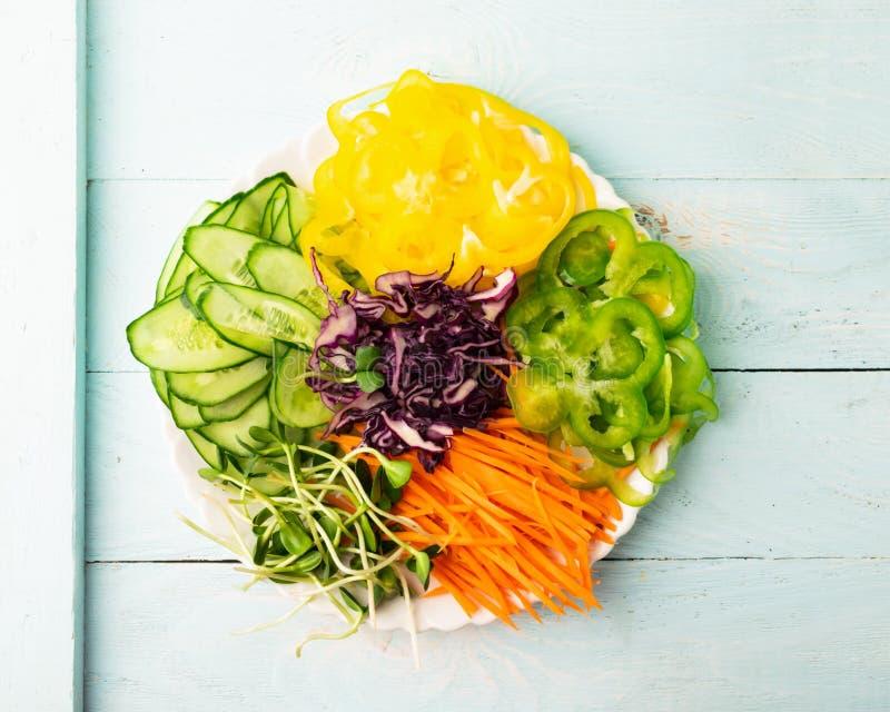 新鲜的未加工的各种各样的菜和年轻绿色新芽在白色盘 健康适当的营养概念 素食主义 免版税库存照片