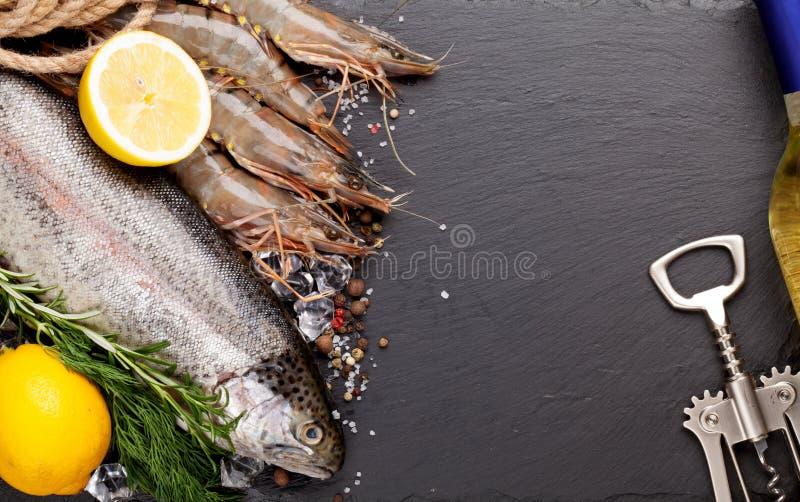 新鲜的未加工的海鲜用香料和白葡萄酒瓶 免版税库存图片