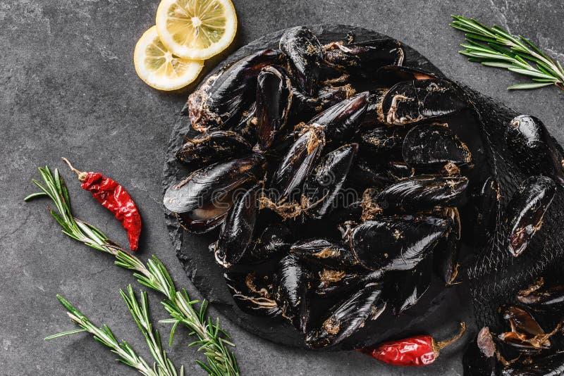 新鲜的未加工的淡菜用在板岩石头的香料在黑暗的背景 海鲜,顶视图,平的位置,拷贝空间 免版税库存图片