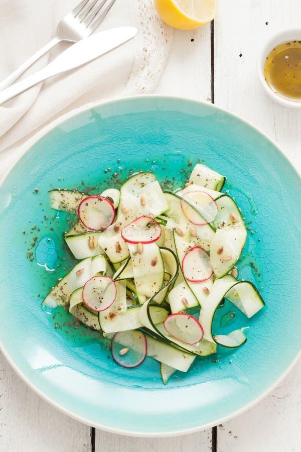 新鲜的未加工的食物的饮食沙拉-夏南瓜'tagliatelle',萝卜切片,烤了向日葵种子 免版税库存照片