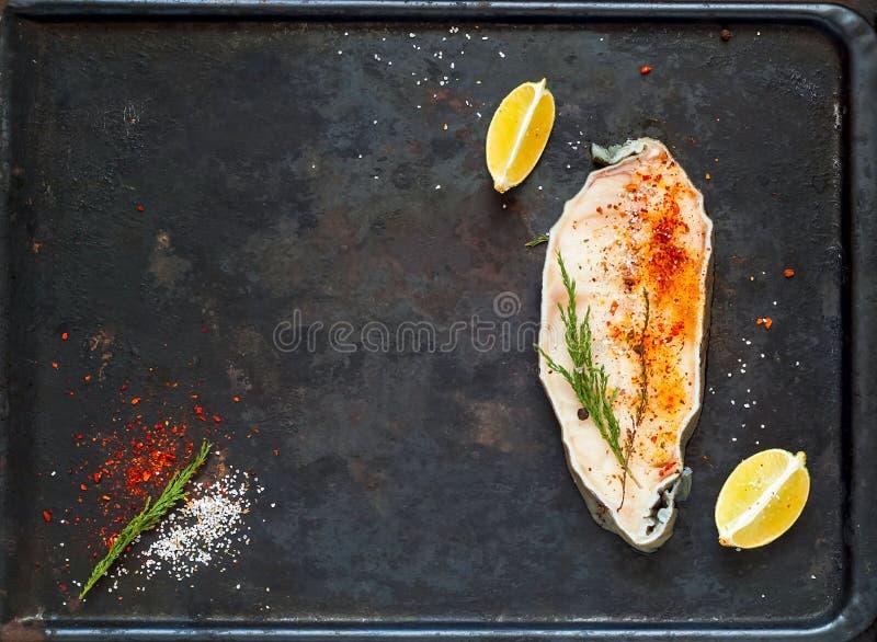新鲜的未煮过的鱼排用柠檬和香料健康烹调的在老生锈的金属背景  平的位置 顶视图 库存照片