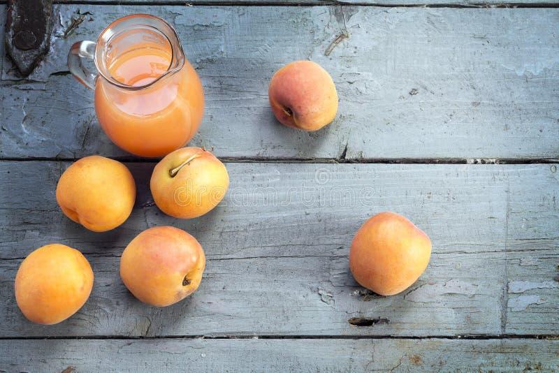 新鲜的杏子和汁液在一个玻璃水罐在土气灰色蓝色求爱 库存照片