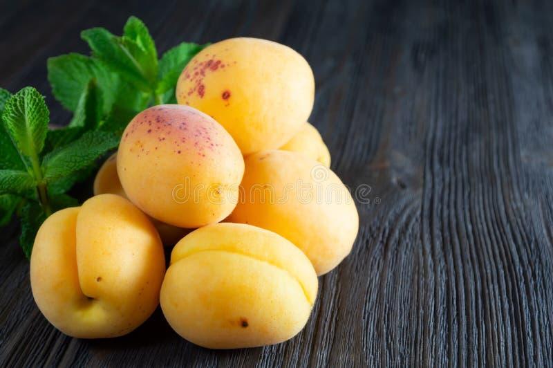 新鲜的杏子和薄荷叶在黑暗的木背景 库存图片