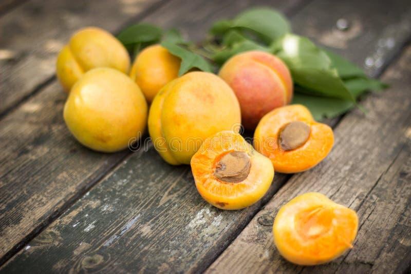 新鲜的杏子在老木桌面驱散了 免版税库存图片