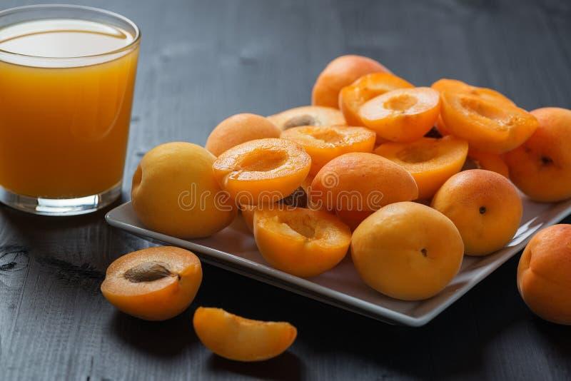 新鲜的杏子汁和杏子在一张木黑桌上 库存图片