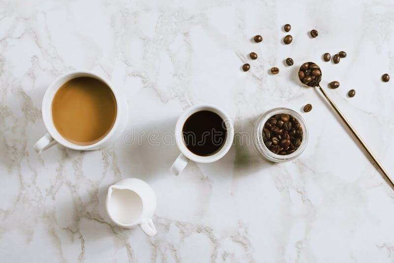 新鲜的杯子Flatlay浓咖啡和牛奶咖啡、盛奶油小壶、咖啡豆和匙子在大理石 免版税库存图片
