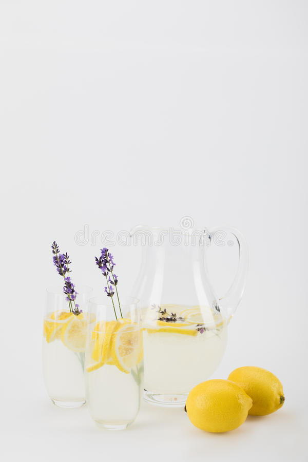 新鲜的柑橘喝与在玻璃的淡紫色花 库存图片