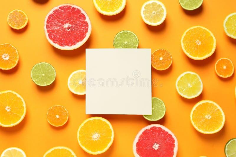 新鲜的柑橘水果和空插件在颜色背景,平的位置 免版税库存照片