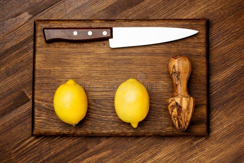 新鲜的柠檬和刀子在木砧板 免版税库存图片