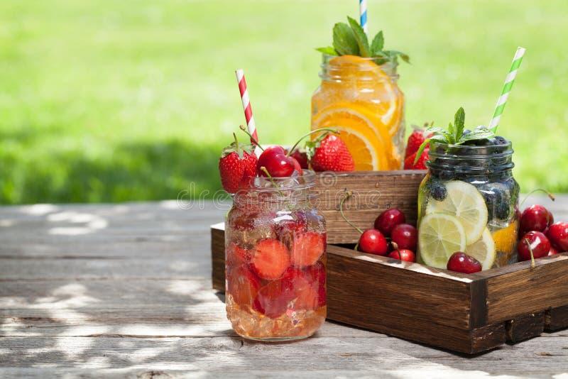 新鲜的柠檬水瓶子用夏天果子和莓果 免版税库存照片