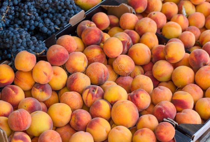 新鲜的桃子和葡萄在市场上 库存照片