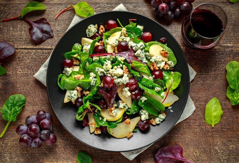 新鲜的梨,与菜绿色混合,核桃,红葡萄的青纹干酪沙拉 健康的食物 库存照片