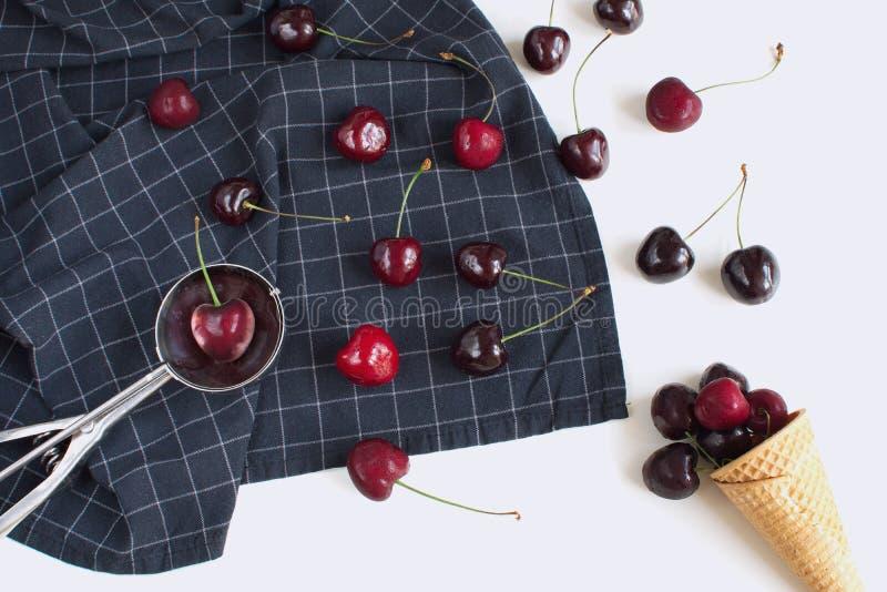 新鲜的樱桃和奶蛋烘饼锥体在方格的餐巾 库存图片