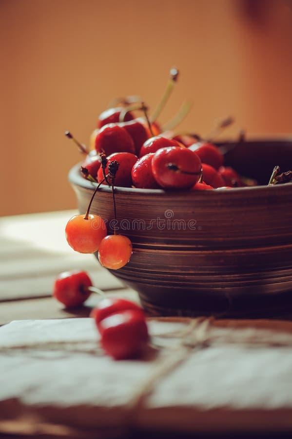 新鲜的樱桃在木桌上的黏土手工制造板材关闭  免版税库存照片