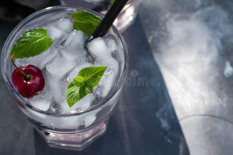 新鲜的樱桃鸡尾酒 新鲜的夏天鸡尾酒用樱桃和冰块 杯樱桃在黑暗的石头的苏打饮料 图库摄影