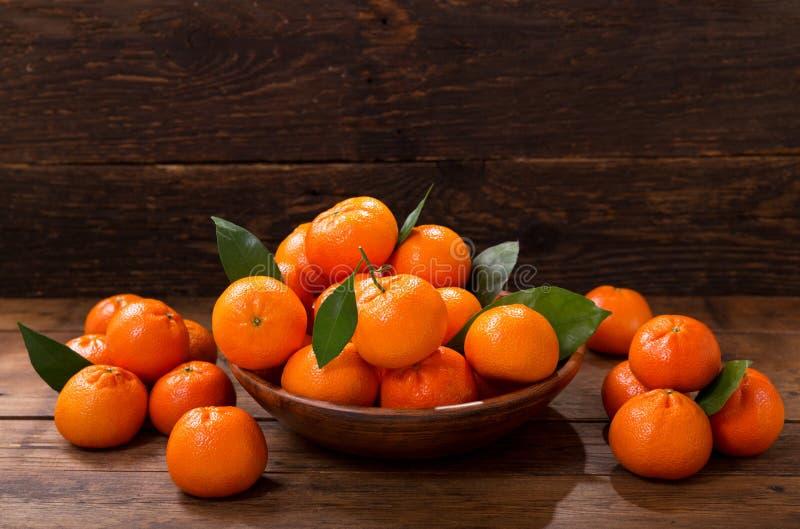 新鲜的橘子结果实或与叶子的蜜桔在碗 免版税图库摄影