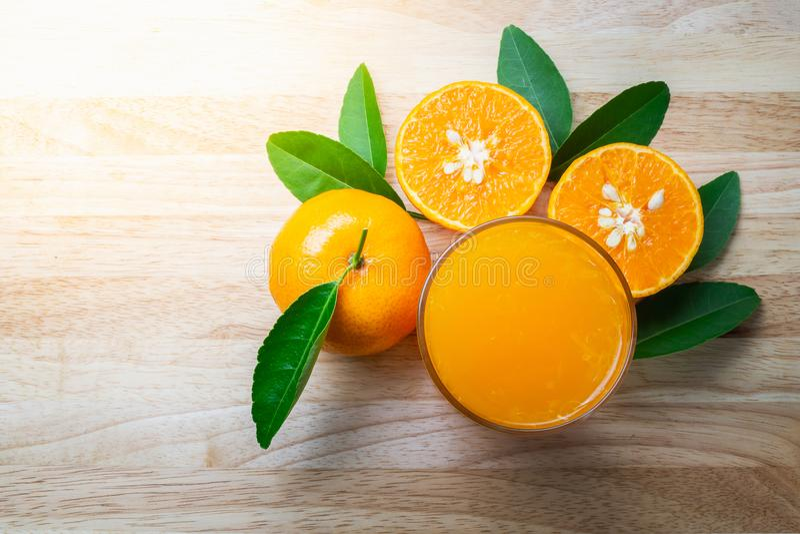 新鲜的橙色果子用在木桌背景的绿色叶子和玻璃汁液 图库摄影