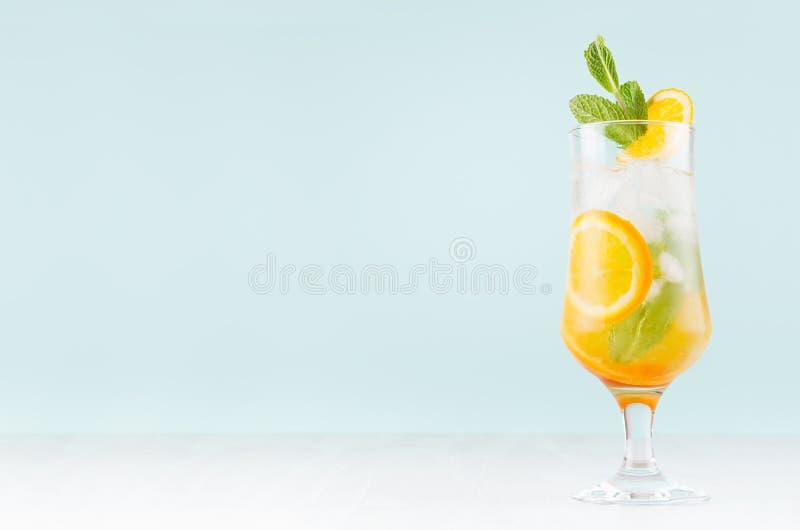 新鲜的橙色鸡尾酒用切片果子,薄菏,秸杆,在misted玻璃的冰块在白色木桌和蓝色墙壁上 库存照片