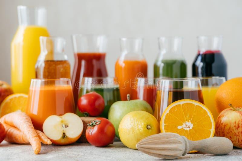新鲜的水果和蔬菜水平的射击在白色桌、玻璃瓶子汁液和橙色剥削者上 健康饮料概念 免版税库存图片