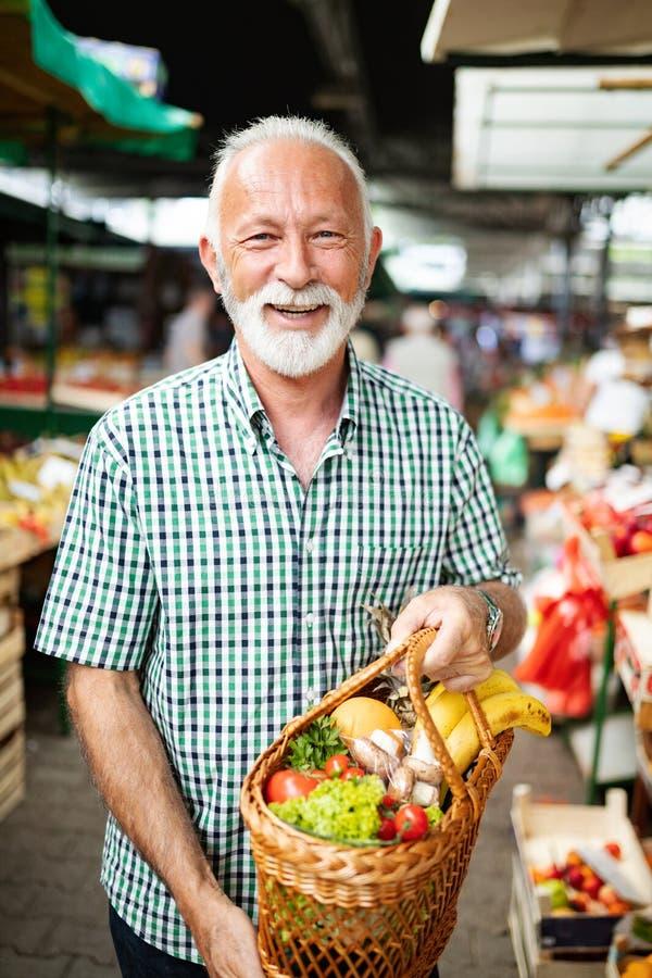 新鲜的水果和蔬菜的英俊的老人购物在市场上 免版税图库摄影
