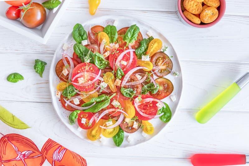 新鲜的沙拉用五颜六色的蕃茄、乳酪、葱和菠菜在白色背景 顶视图 免版税库存图片