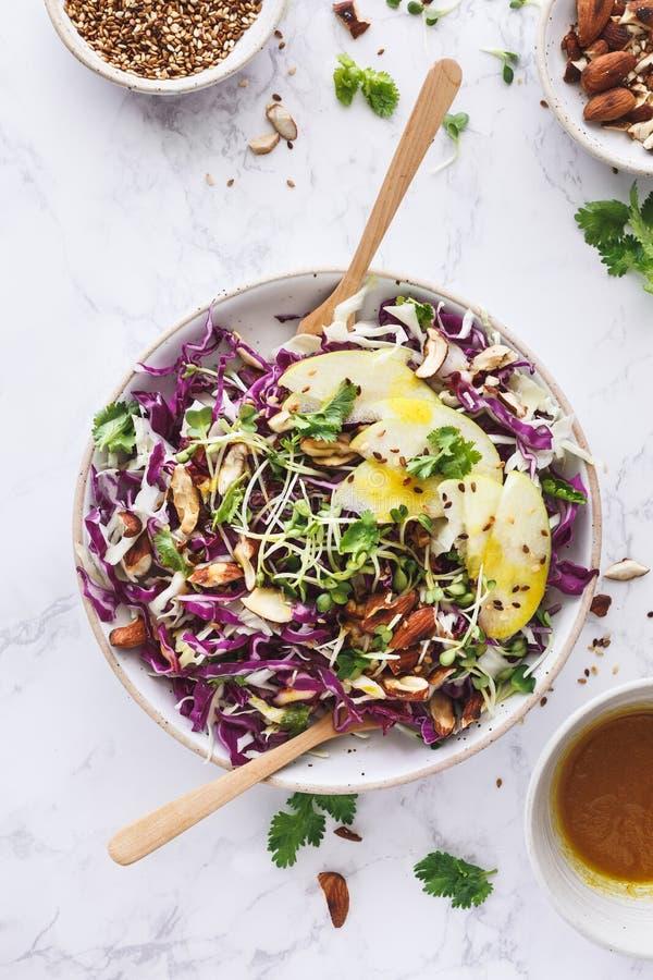 新鲜的沙拉用红叶卷心菜,圆白菜,杏仁,苹果计算机,芝麻,发芽了种子和姜黄调味汁 免版税库存照片